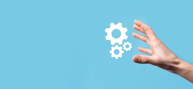 Mão masculina segurando o ícone de engrenagens, ícone do mecanismo em telas virtuais sobre fundo azul.