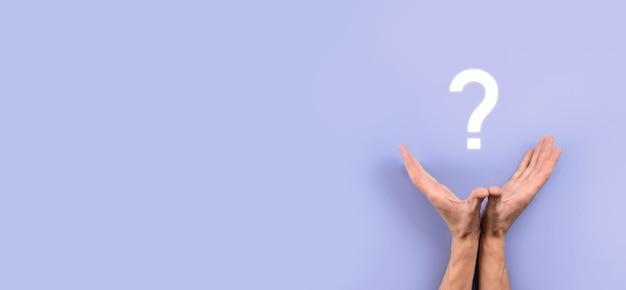 Mão masculina segurando o ícone de ponto de interrogação em fundo escuro. bandeira com espaço de cópia. lugar para texto.