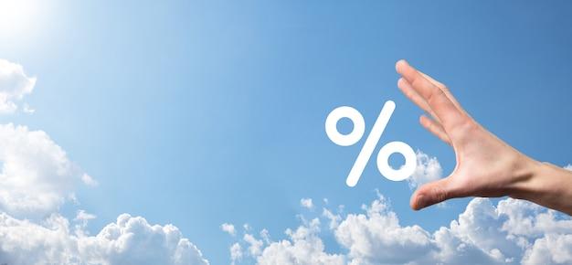 Mão masculina segurando o ícone de porcentagem da taxa de juros na superfície do céu azul