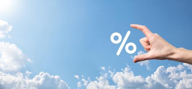 Mão masculina segurando o ícone de porcentagem de taxa de juros no fundo do céu azul. conceito de taxas financeiras e hipotecárias de taxa de juros. bandeira com espaço de cópia.