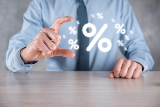 Mão masculina segurando o ícone de porcentagem de taxa de juros sobre fundo azul. conceito de taxas financeiras e hipotecárias de taxa de juros. banner com espaço de cópia