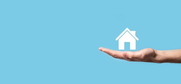 Mão masculina segurando o ícone de uma casa na superfície azul