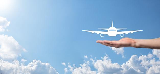 Mão masculina segurando o ícone do avião na superfície azul
