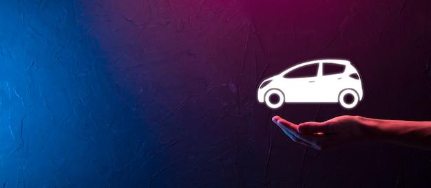 Mão masculina segurando o ícone do carro auto em fundo azul vermelho neon. composição de faixa ampla. conceitos de seguro de automóvel e isenção de danos por colisão
