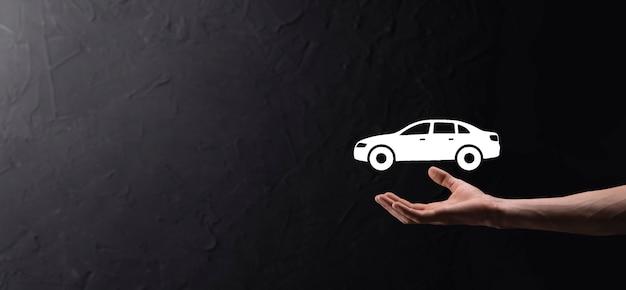 Mão masculina segurando o ícone do carro auto sobre fundo azul. composição de faixa ampla. conceitos de seguro de automóvel e isenção de danos por colisão