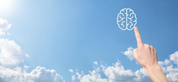 Mão masculina segurando o ícone do cérebro sobre fundo azul. inteligência artificial machine learning business internet technology concept.banner com espaço de cópia.