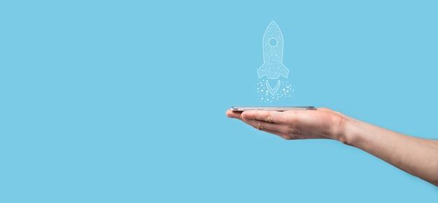 Mão masculina segurando o ícone do foguete digital transparente. conceito de negócio de inicialização. foguete está sendo lançado e voa alto. conceito de ideia de negócio. Foto Premium