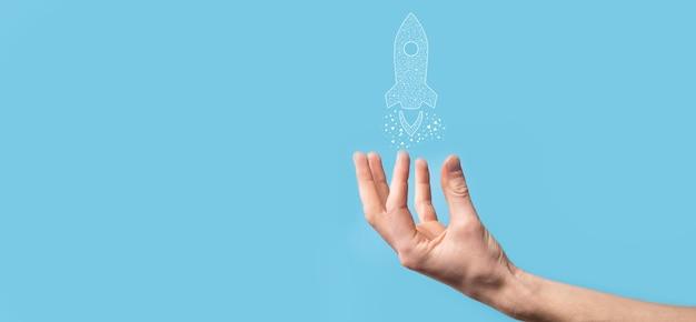 Mão masculina segurando o ícone do foguete digital transparente. conceito de negócio de inicialização. foguete está sendo lançado e voa alto. conceito de ideia de negócio.