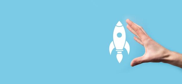 Mão masculina segurando o ícone do foguete que decola, lançamento em fundo azul. foguete está lançando e voando para fora, arranque de negócios, marketing de ícone na interface virtual moderna. conceito de inicialização.