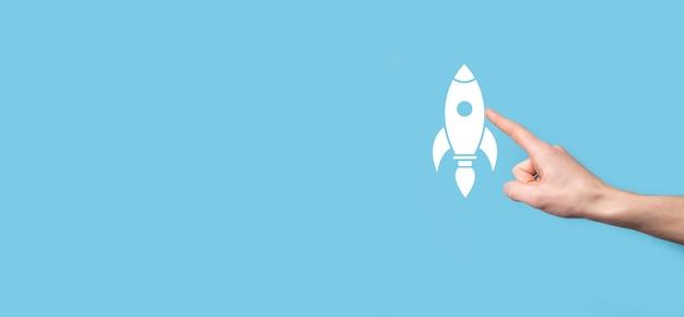 Mão masculina segurando o ícone do foguete que decola, lançamento em fundo azul. foguete está sendo lançado e voando para fora, arranque de negócios, marketing de ícone na interface virtual moderna. conceito de inicialização.