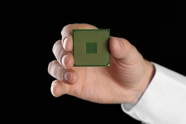 Mão masculina segurando o microprocessador preto