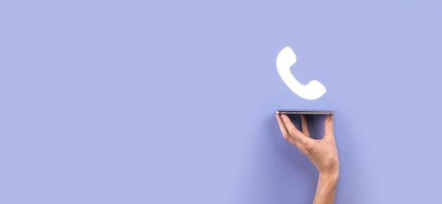 Mão masculina segurando o telefone móvel inteligente com o ícone do telefone. ligue agora para o conceito de tecnologia de serviço ao cliente do centro de suporte de comunicação empresarial.