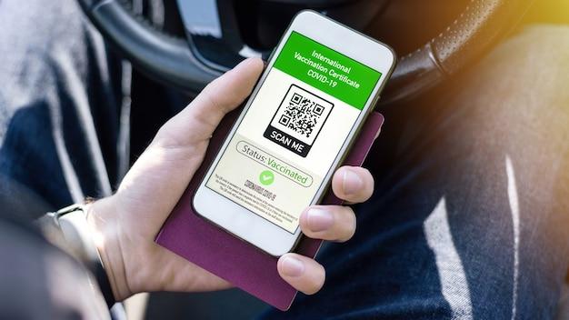 Mão masculina segurando passaporte e smartphone com código qr covid-19 do certificado de vacinação internacional em um carro