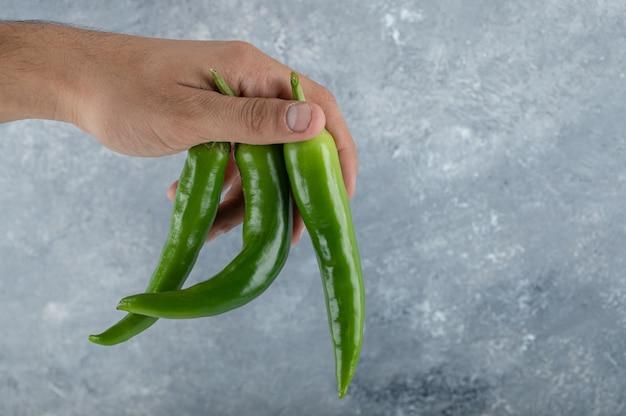 Mão masculina segurando pimenta verde no ar.