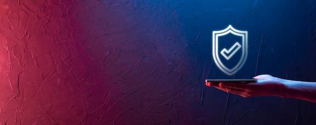 Mão masculina segurando protege o escudo com um ícone de marca de seleção sobre fundo azul. proteção de rede de segurança de computador e proteção de seu conceito de dados.
