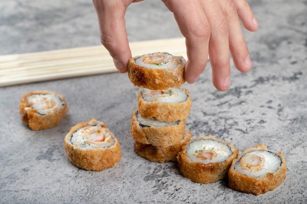 Mão masculina segurando rolo de sushi frito quente perto de pauzinhos de madeira descartáveis.