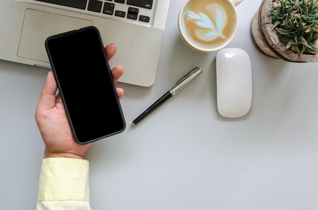 Mão masculina segurando smartphone, computador, caneta, café, mouse na mesa da mesa do escritório com espaço de cópia