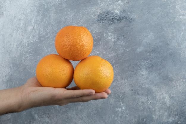 Mão masculina segurando três laranjas na mesa de mármore.