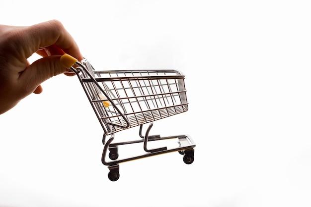 Mão masculina segurando um carrinho de compras em branco