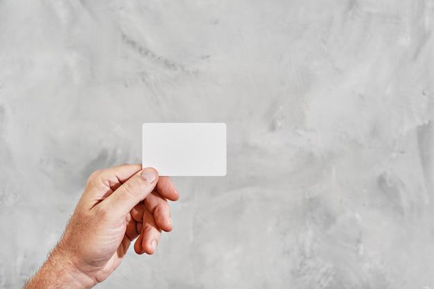 Mão masculina segurando um cartão branco em branco isolado contra um fundo cinza neutro. cartão de visita na mão
