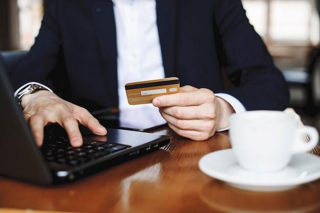 Mão masculina segurando um cartão de crédito durante a operação em um laptop sentado em uma mesa, bebendo café.