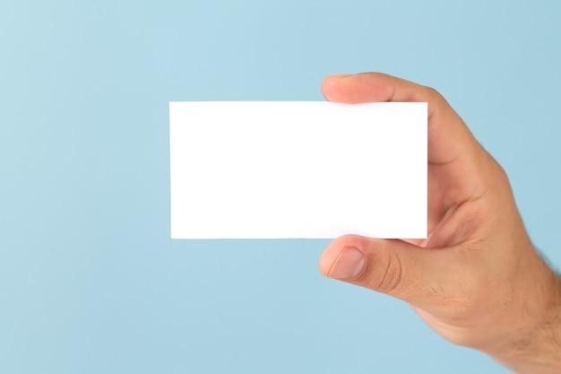 Mão masculina segurando um cartão de visita em branco sobre fundo azul claro