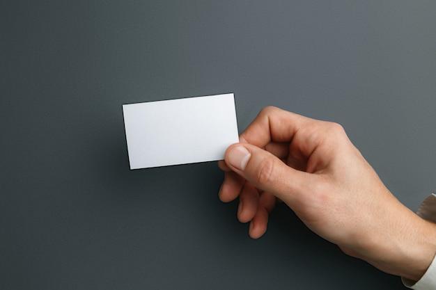 Mão masculina segurando um cartão de visita em branco sobre fundo cinza para texto ou desenho