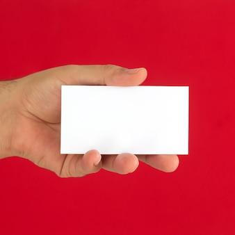 Mão masculina segurando um cartão de visita em branco sobre fundo vermelho