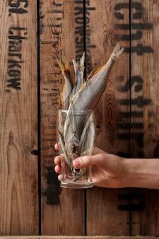 Mão masculina segurando um copo com sabrefish salgado seco ao ar