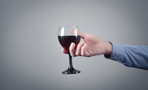 Mão masculina segurando um copo de vinho tinto.