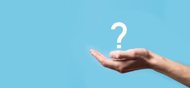 Mão masculina segurando um ícone de ponto de interrogação na superfície azul