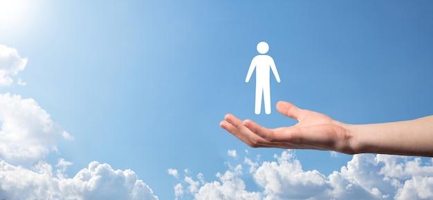 Mão masculina segurando um ícone humano sobre fundo azul. recursos humanos gestão de rh recrutamento emprego headhunting concept.selecione o conceito de líder de equipe. mão masculina, clique no ícone do homem. banner, cópia spase.