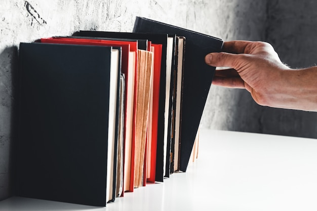 Mão masculina segurando um livro de estantes