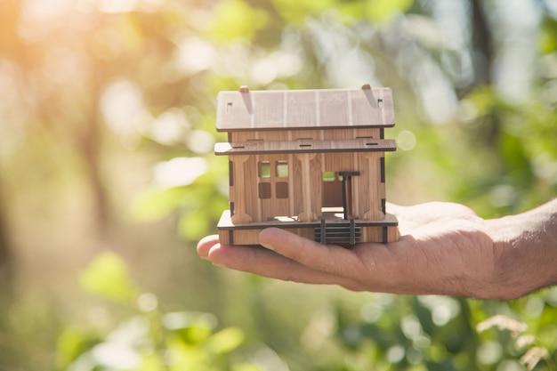 Mão masculina segurando um modelo de casa de madeira na natureza.