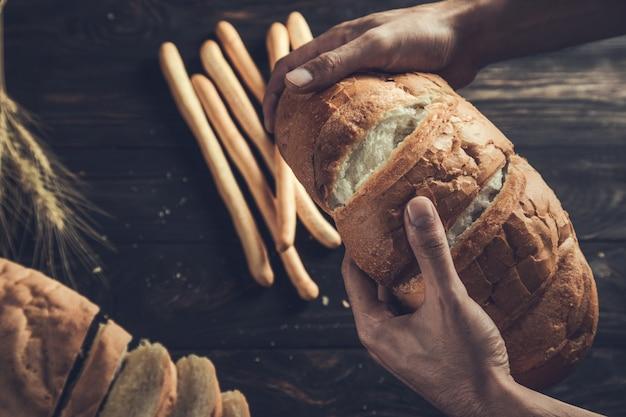 Mão masculina segurando um pão rústico fresco