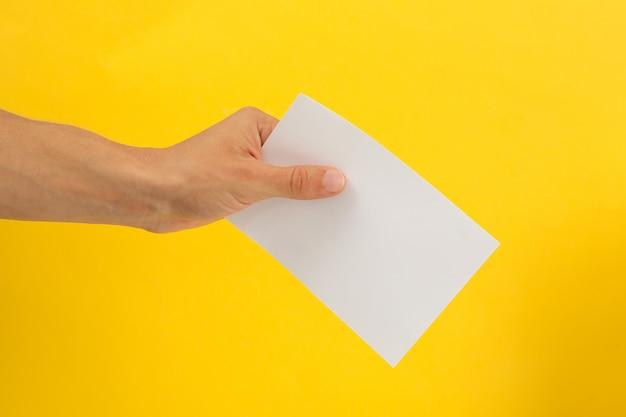 Mão masculina segurando um papel em branco na superfície amarela