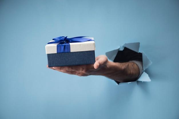 Mão masculina segurando um presente em uma cena azul