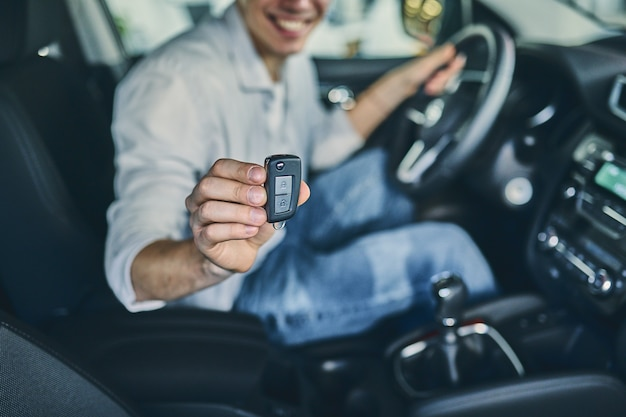 Mão masculina segurando um volante antes de comprar um automóvel novo no showroom