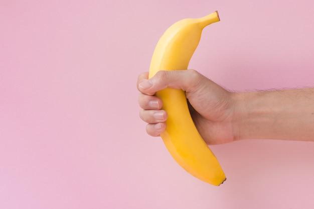 Mão masculina segurando uma banana isolada no fundo rosa.