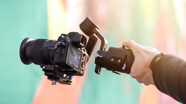 Mão masculina segurando uma câmera na steadycam, fundo colorido