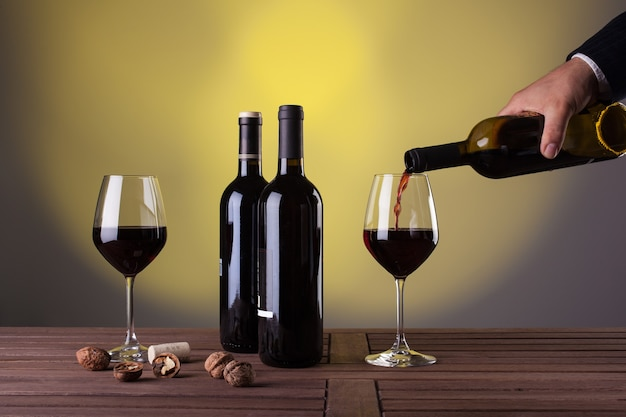 Mão masculina segurando uma garrafa de vinho tinto e servindo em uma taça de vinho