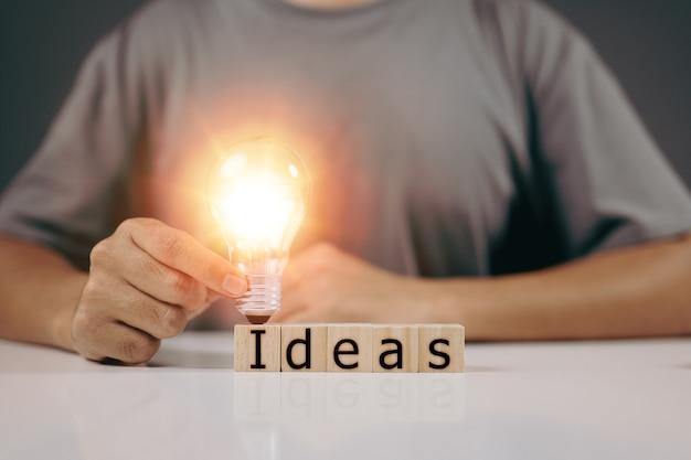 Mão masculina segurando uma lâmpada, uma nova ideia e criatividade, inovação e conceito de inspiração