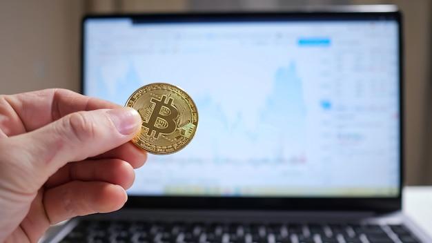 Mão masculina segurando uma moeda de criptomoeda sobre o fundo do laptop, mostrando o gráfico