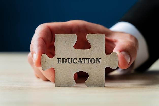 Mão masculina segurando uma peça do quebra-cabeça com placa de educação.