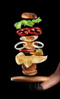 Mão masculina segurando uma placa de madeira redonda e camadas flutuantes de cheeseburguer com ovo de galinha e costeleta de carne em fundo preto, fast food
