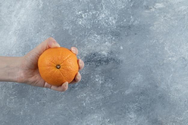 Mão masculina segurando uma única laranja na mesa de mármore.