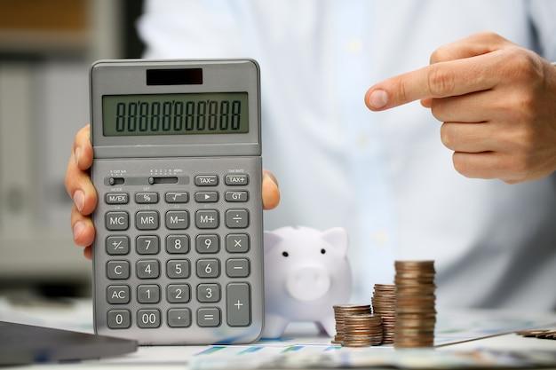 Mão masculina segurar calculadora na mão configuração de escritório em casa.