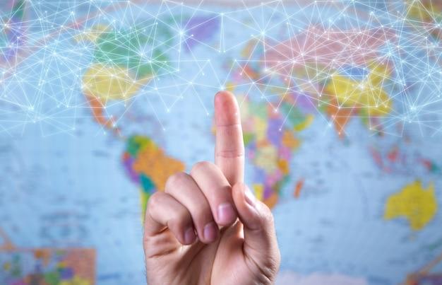 Mão masculina tocando em rede no fundo do mapa do mundo.