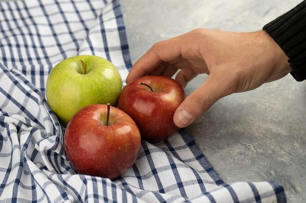 Mão masculina tomando maçã vermelha fresca de mármore.
