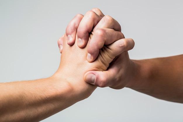 Mão masculina unida em um aperto de mão. homem ajuda as mãos, tutela, proteção. duas mãos, braço isolado, mão amiga de um amigo. aperto de mão amigável, amigos cumprimentando.